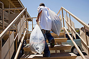 22 JUNE 2009 - PHOENIX, AZ: A volunteer at the Cultural Cup carries donated clothes up to the food bank's storage rooms. The Cultural Cup has become a sort of community center. It started as a food bank and has since grown to include a clothing bank and free walk in clinic. The walk in clinic at the Cultural Cup Food Bank started two years ago when Cultural Cup founder Zarinah Awad wanted to expand the food bank's outreach and provide basic medical care for the people who use the food bank. The clinic sees, on average, 7 - 11 patients a week. Awad said that as the economy has worsened since the clinic opened and demand has steadily increased. She attributes the growth to people losing their jobs and health insurance. The clinic is staffed by volunteers both in the office and medical staff. Adults are seen every Saturday. Children are seen one Saturday a month, when a pediatrician comes in. Awad, a Moslem, said the food bank and clinic are rooted in the Moslem tradition of Zakat or Alms Giving, the giving of a small percentage of one's income to charity which is one of the Five Pillars of Islam.   PHOTO BY JACK KURTZ