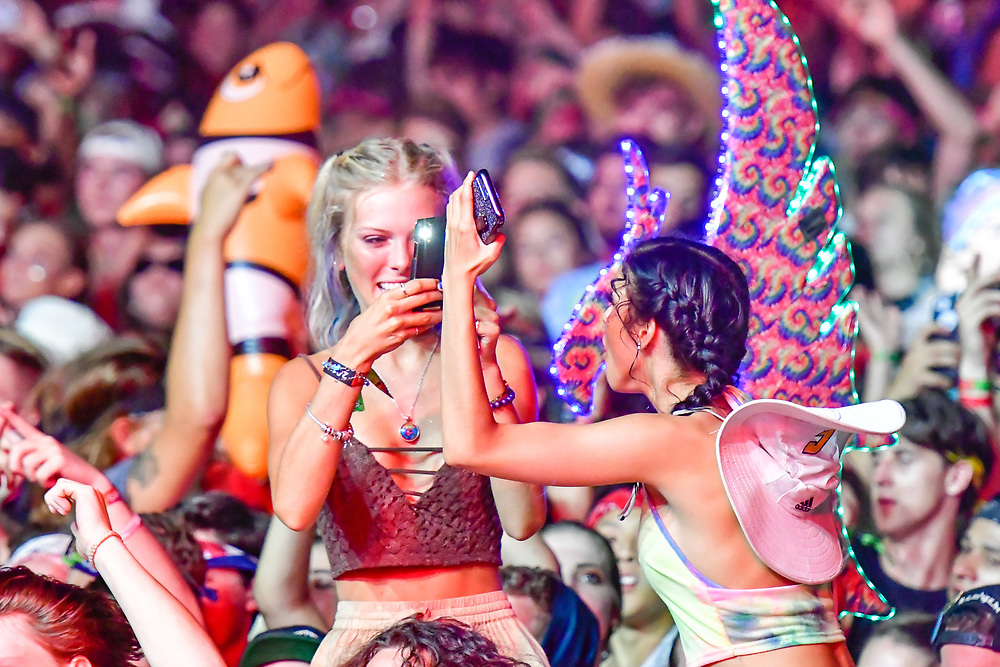 A festival attendee poses as her friend takes her picture during a set at The Other Stage during The Bonnaroo Music and Arts Festival in Manchester, TN