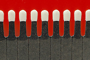 close up of wooden matches on bright red background