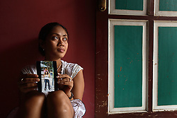 Lisa, 29, holds up a photo of her with her best friend Dede, 25, who died in 2003 from an unsafe abortion, Jakarta, Indonesia, April 24, 2006. The photo was taken the day before Dede was rushed to hospital with severe bleeding, where she died three days later. It is said by doctors and activists that a woman dies every hour in Indonesia due to unsafe abortions.