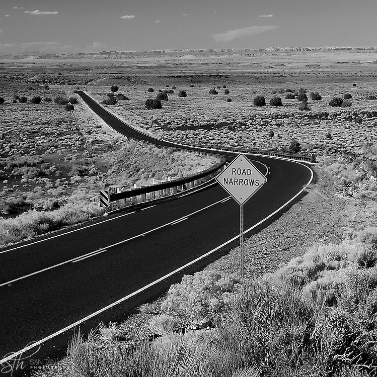 The road between Sunset Crater and Wupatki National Monument, with the Painted Desert in the distance