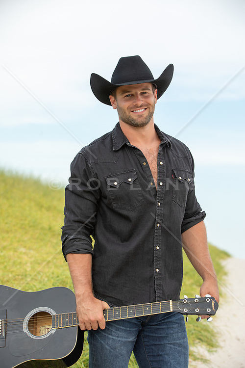 hot cowboy with a guitar outdoors