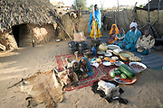 The Mustapha family in their courtyard in Dar es Salaam village, Chad, with a week's worth of food. Gathered around Mustapha Abdallah Ishakh, 46 (turban), and Khadidja Baradine, 42 (orange scarf), are Abdel Kerim, 14, Amna, 12 (standing), Nafissa, 6, and Halima, 18 months. Lying on a rug are (left to right) Fatna, 3, granddaughter Amna Ishakh (standing in for Abdallah, 9, who is herding), and Rawda, 5. The Mustapha family is one of the thirty families featured in the book Hungry Planet: What the World Eats (p. 68).