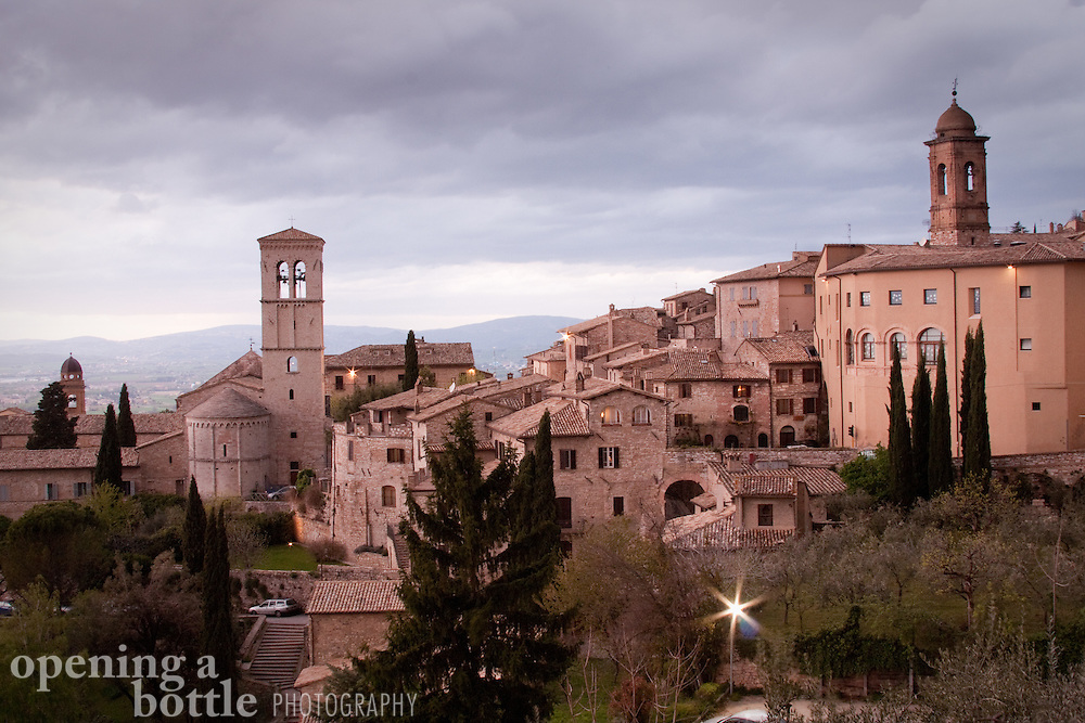 Bell towers rise over the skyline of Assisi at dusk, as seen from the Piazza Santa Chiara. Assisi, Umbria, Italy.