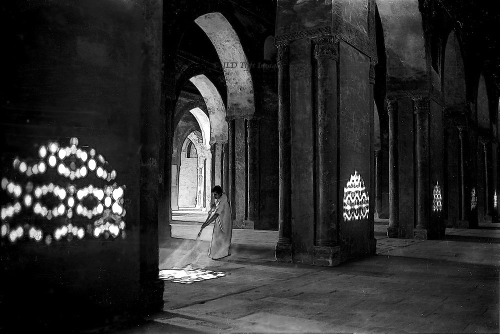 Mosque caretaker sweeping the floor seems to be sweeping the sunlight projected from windows on the exterior wall.    Their Islamic piercing pattern also projects onto the mosque pillars.  BAround and behind the sweeper, the pointed arches recede, also illuminated by sunlight.   This is a rare image of the mosque interior.