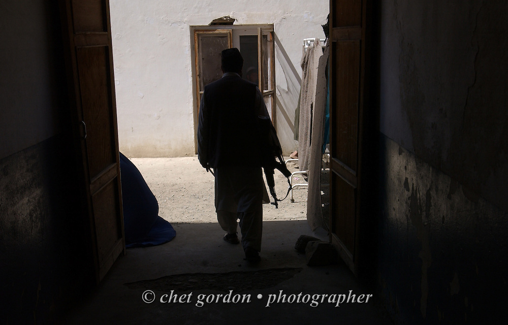 """An Afghan man with an automatic weapon walks out of the Charasyab health clinic approximately 20 kilometers outside of Kabul, Afghanistan on Sunday, May 26, 2002. A humanitarian mission organized by The Geshundheit Instititute, founded by Dr. Hunter """"Patch"""" Adams, Lufthansa Cargo, and DHL Worldwide Express collaborated to ship medicines, food and orthopedic supplies to the Indira Ghandi Children's Hospital, clinics and orphanages in Kabul. The German NGO (Non Governmental Organization) Hammer Forum supervised the distribution of the donated supplies from various non-profit organizations in the U.S. and The Netherlands."""