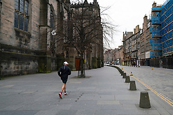 Edinburgh, Scotland, UK. 24 March, 2020.  Deserted streets in the heart of the Old Town tourist district in Edinburgh. All shops and restaurants are closed with very few people venturing outside following the Government imposed lockdown today. Pictured; Runner makes his way past St Giles Cathedral on an empty Royal Mile. Iain Masterton/Alamy Live News
