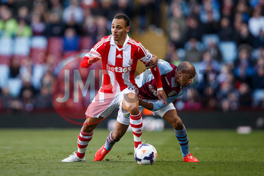 Stoke Forward Peter Odemwingie (NGA) is challenged by Aston Villa Midfielder Fabian Delph (ENG) - Photo mandatory by-line: Rogan Thomson/JMP - 07966 386802 - 23/03/2014 - SPORT - FOOTBALL - Villa Park, Birmingham - Aston Villa v Stoke City - Barclays Premier League.