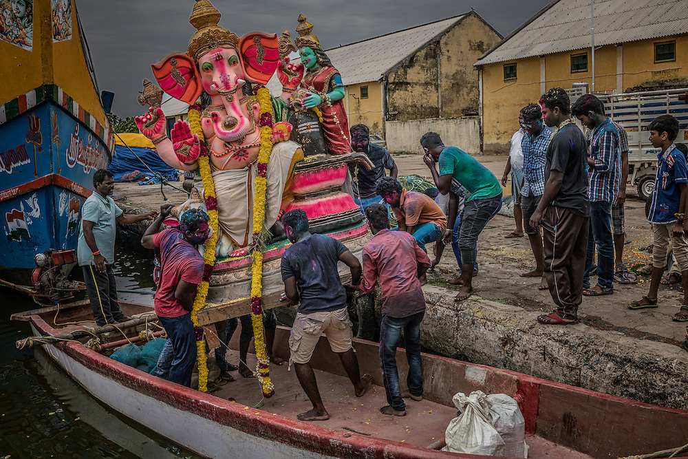 Men load a Lord Ganesha statue on a small boat in the fishing port in Pondicherry to bring it out to sea to return it to nature as part of the Ganesh Chaturthi festival.  Pondicherry, India.