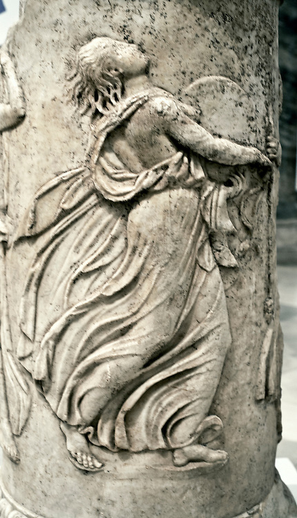 Relief sculpture of a dancing maenad in a procession, carved on a cylindrical base.  She holds a drum; her dress and drapery swirl joyfully about her.