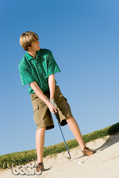 Young Man Hitting Ball in Sand Trap