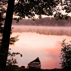A canoe rests on the shore of Pawtuckaway Lake at dawn as seen from Horse Island in New Hampshire's Pawtuckaway State Park.