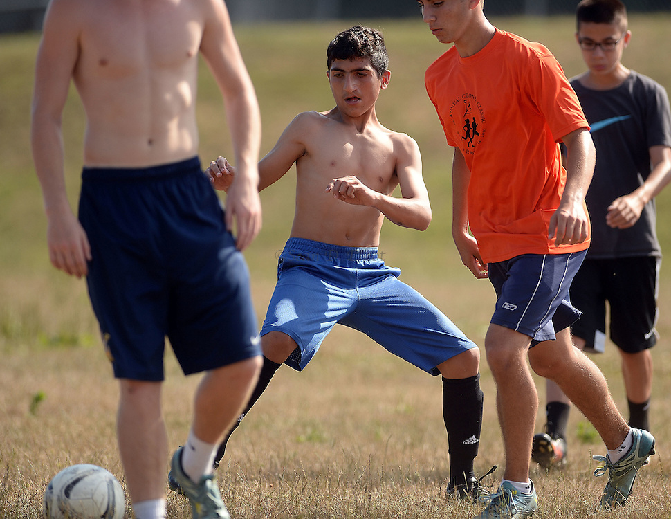 7/21/16 :: REGION :: LYNCH :: Hanif Mahmud plays pick-up soccer with prospective members of the soccer team at Ledyard High School Thursday, July 21, 2016 following a conditioning workout with the team's coach. The Mahmud family, Hassan and Fahima Jmoo and their children Hanif, Fidan and Fulla live in a rented Ledyard home. The family are refugees from the conflict in Syria and lived for three years in Turkey before finally receiving approval to come to the United States. The volunteers are: Rich and Bonnie Denton and their son Henry, 11 and Sarah Holdridge. Translators Zin Arnaout and Yomen Arnaout joined later. (Sean D. Elliot/The Day)
