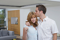 Couple embracing woman holding key in new home