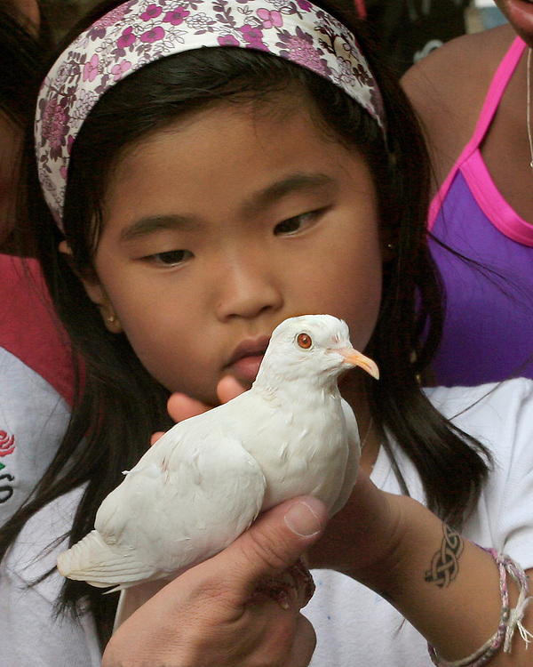 A magician at a local Brooklyn block party produces a pigeon for a curious young girl.