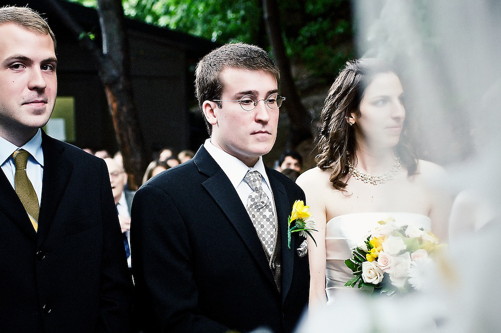 The groom's brother casts a look towards the photographer while capturing this moment during the wedding ceremony.