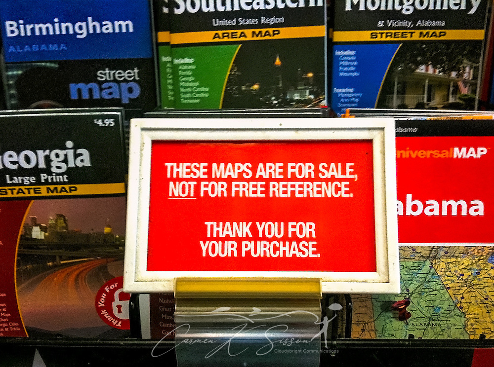 A convenience store sign reminds customers that the maps are for sale, not free reference. (Photo by Carmen K. Sisson/Cloudybright)