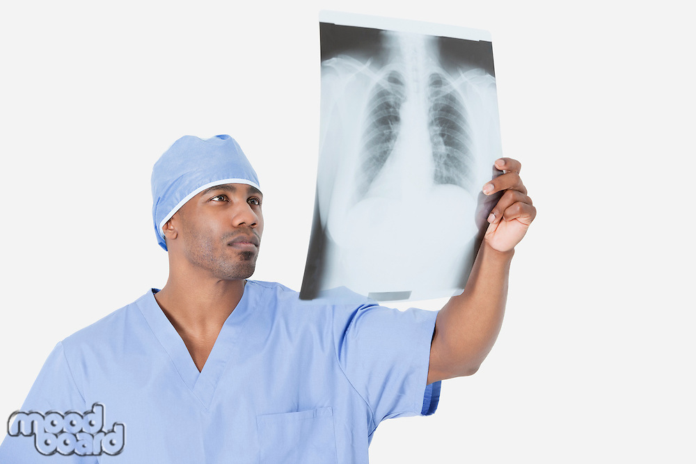 Male surgeon analyzing x-ray report over gray background