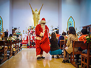 24 DECEMBER 2013 - BANGKOK, THAILAND: Santa Claus delivers candy to parishioners during Christmas services at Holy Redeemer Church in Bangkok. Thailand is predominantly Buddhist but Christmas is widely celebrated throughout the country. Buddhists mark the day with secular gift giving but there are about 300,000 Catholics in Thailand who celebrate religious Christmas. Catholics first came to Thailand (then Siam) in 1567 as chaplain for Portuguese mercenaries in the employ of the Siamese monarchy. There has been a continuous Catholic presence in Thailand since then.   PHOTO BY JACK KURTZ