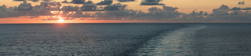 The sun rises astern of Queen Mary 2, during the Transatlantic Fashion Week voyage en route to New York. During the trip passengers will rub shoulders with award winning British fashion designer Julien Macdonald OBE who will put on two runway shows plus other events.<br /> Date: Friday September, 1; 2017.<br /> For the second year running, the Transatlantic Fashion Week will bring together some of the most reputable names within the fashion industry to host seven days of shows, inspiring talks, glamorous dinners and exclusive unveilings. The crossing will arrive in to New York on the 7th September the very same day as New York Fashion Week 2017 begins.<br /> Photograph by Christopher Ison &copy; for Cunard.<br /> 07544044177<br /> chris@christopherison.com<br /> www.christopherison.com