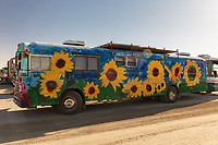 RV with sunflowers and solar panels.