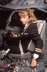 Female pilot sitting at aeroplane controls,