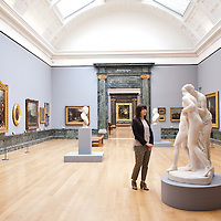 "London, UK - 13 May 2013: A Tate employee poses for a picture next to a marble sculpture  entitled ""Hylas Surprised by the Naiades 1827-36"" by John Gibson in the 1810 room. The new chronological presentation of the world's greatest collection of British art will allow visitors to experience the national collection of British art in a continuous chronological display from the 1500s to the present day."
