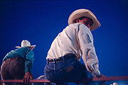 Cowboy sitting on the perimeter fence of a rodeo arena looking at the camera during the county fair in Meredosia, Illinois