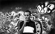 Teenager smoking a spliff in front of a graffiti covered wall, London, Uk, 2000's