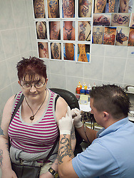 Person with disability having a tattoo in tattoo parlour - applying tattoo