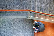 Nederland, the Netherlands, 20-4-2016Een student, jongere, is in een gang, hal van een gebouw bezig met zijn mobiel .Younster busy with his cell phoneFOTO: FLIP FRANSSEN/ HH