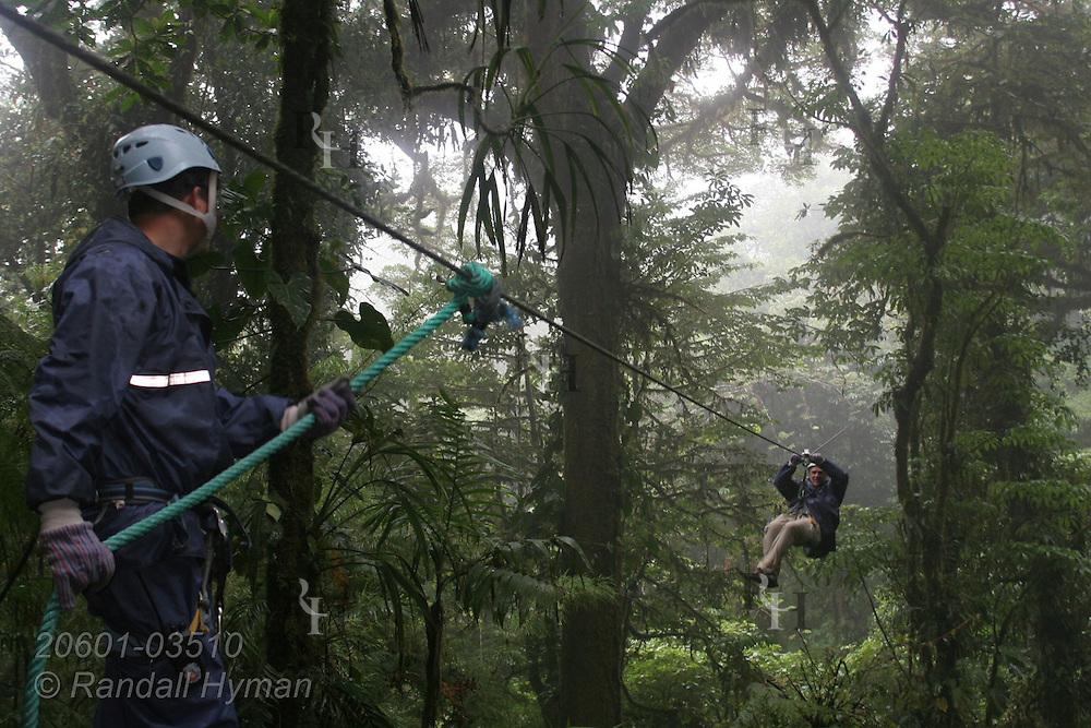 Ecoteach participant Gordon Seibel ziplines through the Monteverde cloud forest on Sky Trek cable as guide awaits his arrival; Monteverde, Costa Rica.