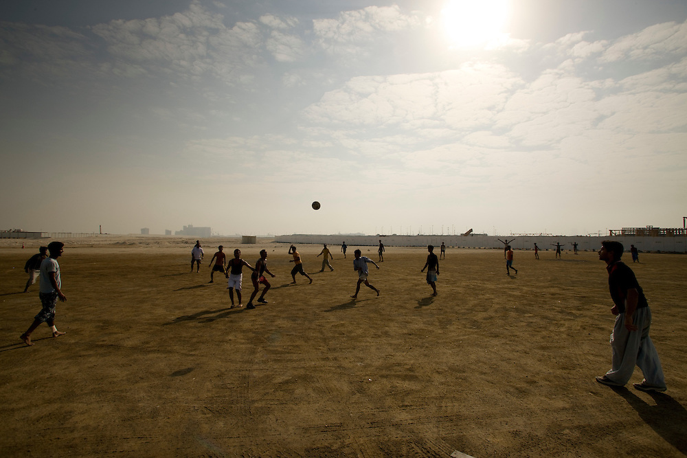 Guest workers play footbal (soccer) duing day off in open ground  ther workplace