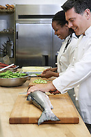 Male chef preparing salmon beside colleague in kitchen