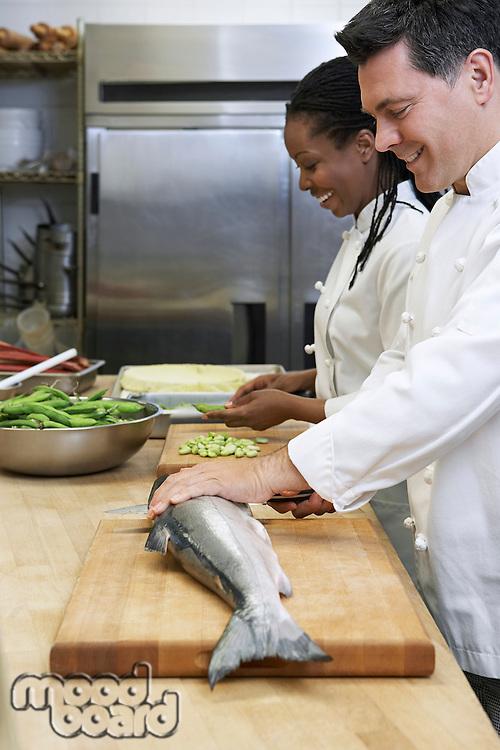 Male chef preparing salmon beside colleague in kitchen