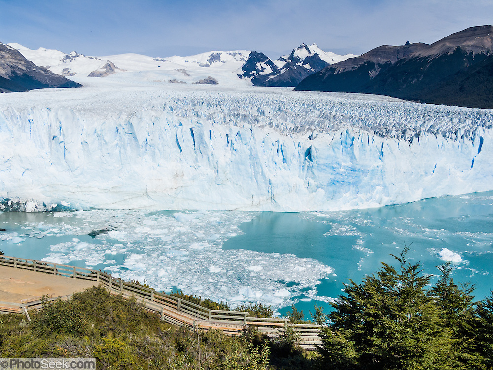 Visit Perito Moreno Glacier in Los Glaciares National Park as a day trip from El Calafate, in southwest Santa Cruz province, Argentina. Easy boardwalks give wide views of Moreno Glacier, an impressive wall of ice 200 feet high and 3 miles (5 km) wide flowing into Lake Argentina. The glacier flows up to 2300 feet thick and originates in the huge Hielo Sur (Southern Icefield) in the southern Andes mountains. For the past 90 years, its advancing has equaled melting (up to 2 meters per day, 700 meters per year), and the terminus has stayed at one location. Flowing ice periodically dams an arm of the lake which rises for a few years then breaks across the nose of the glacier as a crashing river (in March 2004 and 1991). In this 2005 photo, a narrow river flowed across the glacier face which calved large chunks of ice into the water with a loud crash several times per day. The foot of South America is known as Patagonia, a name derived from coastal giants, Patagão or Patagoni, who were reported by Magellan's 1520s voyage circumnavigating the world and were actually Tehuelche native people who averaged 25 cm (or 10 inches) taller than the Spaniards.
