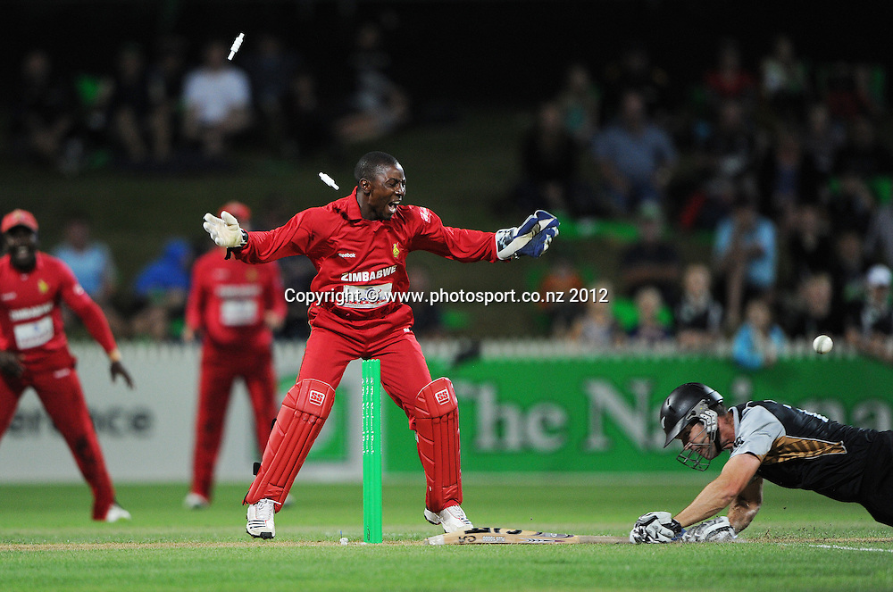 James Franklin is run out after a direct hit by Keegan Meth as wicketkeepr Tatenda Taibu looks on during the 2nd Twenty20 InternationaI cricket match between New Zealand and Zimbabwe at Seddon Park in Hamilton, New Zealand on Tuesday 14 February 2012. Photo: Andrew Cornaga/Photosport.co.nz