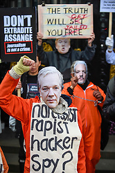 © Licensed to London News Pictures. 22/02/2020. LONDON, UK.   A person wearing a Donald Trump mask with people wearing Julian Assange masks ahead of a march from Australia House in Aldwych to Parliament Square in support of Wikileaks founder Julian Assange.  The full extradition trial of Mr Assange begins in London on 24 February.  Photo credit: Stephen Chung/LNP