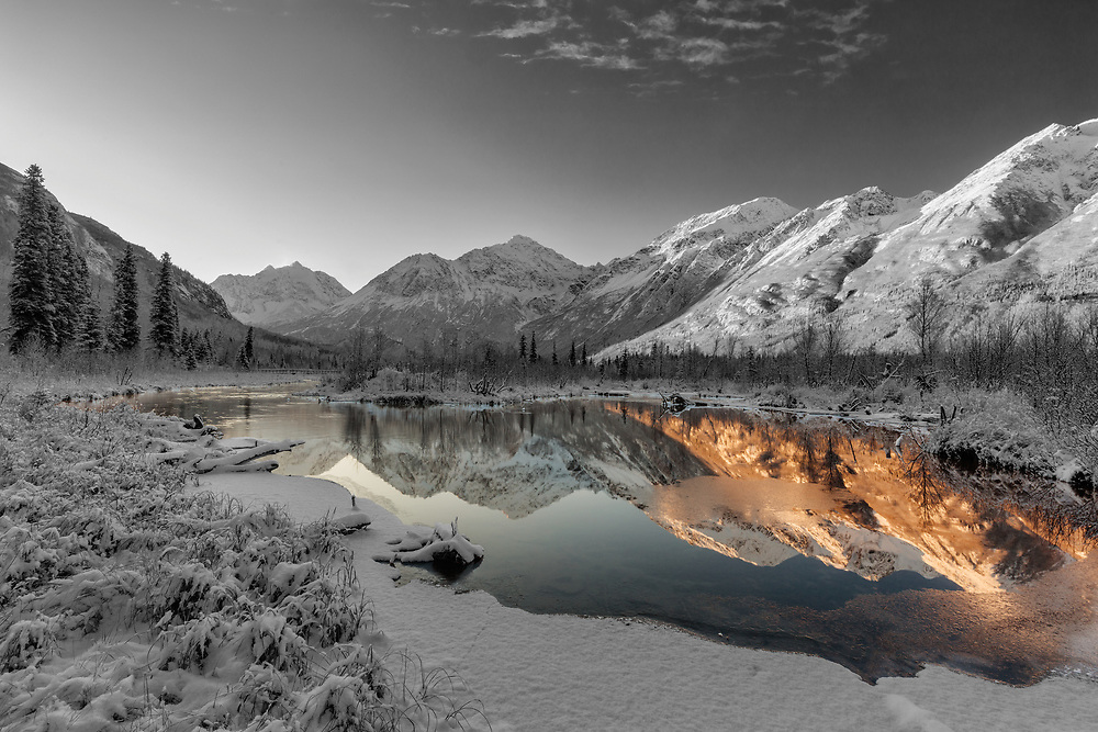 Dawn light illuminates the season's first snow as it blankets Eagle River Valley and the Chugach Mountains in Southcentral Alaska. Winter.