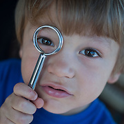 young boy looking through a metal utensil, as if scrutinizing the viewer
