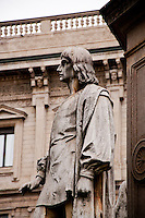 Milan, Italy. Stone statue of a man near the da Vinci monument.