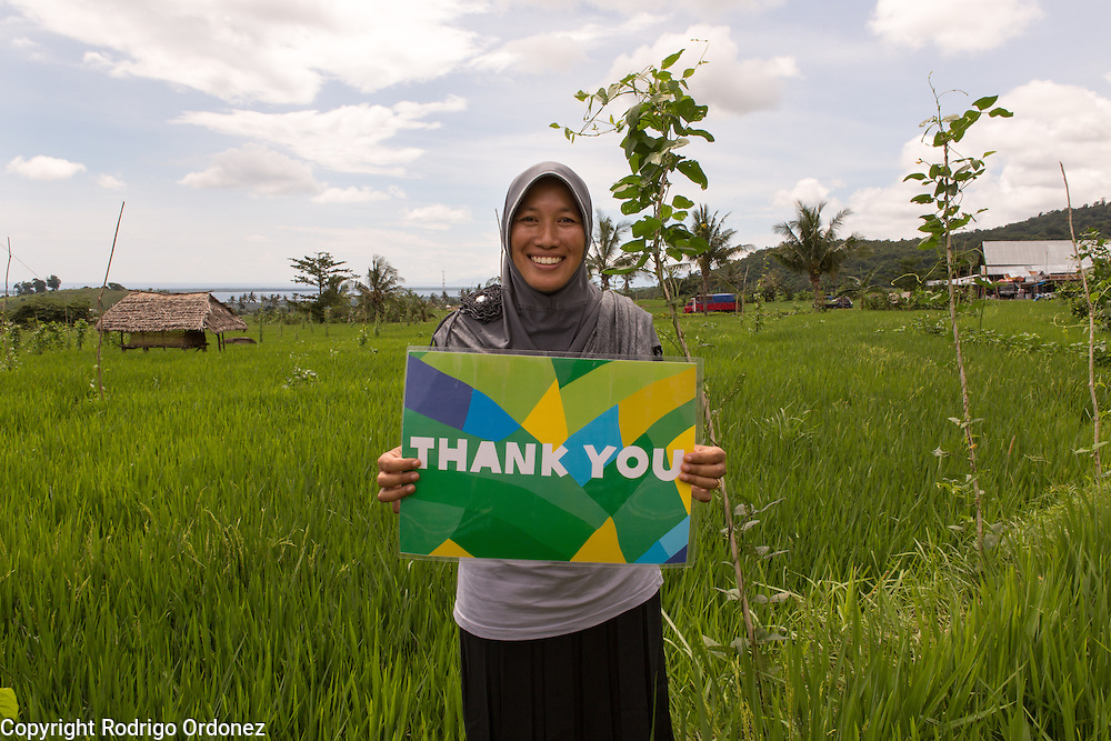 Parhanah, 39, a member of Belanting's emergency preparedness team specialized in logistics, poses for a photograph holding a 'Thank you' sign. Oxfam and its local partner Konsepsi are working with women to strengthen their capacity and improve their leadership skills. Belanting is located in Sambelia district, East Lombok, West Nusa Tenggara province, Indonesia.