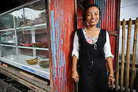 Ibu Buhariah beside her food kiosk at the Jongaya leprosy settlement, Makassar, Sulawesi, Indonesia. Ibu Buhariah, 39, is originally from Panglep, Sulawesi.  She discovered she was infected with leprosy at the age of 7 and received treatment at home and at the Daya leprosy hospital before moving to Jongaya when she was 16.  She married in the settlement in 1998 but has no children.  She runs a small business selling prepared food such as fish, tempe and vegetable dishes.  Up until a year ago, Ibu Buhariah would sell from the side of the road outside her house, but she has now bought a mobile kiosk using a loan from Permata.