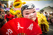 "10 FEBRUARY 2013 - BANGKOK, THAILAND:  A ""Laughing Buddha"" accompanies a parade of Lion Dancers on Chinese New Year in Bangkok. The Buddhas are comic and acrobatic characters who interact with the crowd and tease the lion with a fan or a ball. The lion in turn will play with, chase, or even bite and kick the buddha depending on its mood. Because it is difficult for the lion dancers to see, the Buddhas also help the lions find their ""food"", etc. Bangkok has a large Chinese emigrant population, most of whom settled in Thailand in the 18th and 19th centuries. Chinese, or Lunar, New Year is celebrated with fireworks and parades in Chinese communities throughout Thailand. The coming year will be the ""Year of the Snake"" in the Chinese zodiac.   PHOTO BY JACK KURTZ"