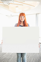 Portrait of confident businesswoman holding blank placard in creative office