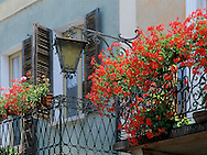 Red geraniums on a balcony in Orta on<br /> Lake Orta, Italy