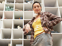 Young Woman leaning on Tool Shelves low angle view portrait