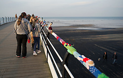 © Licensed to London News Pictures. 16/03/2012..Saltburn Pier, Saltburn, Cleveland..The 50 foot knitted Olympic scarf depicting athletes taking part in various sporting activities and which appeared mysteriously on the Victorian pier at Saltburn recently has had some of the figures ripped from the scarf in an act of mindless vandalism...The Teddy Bears picnic, one of the first knitted displays to appear on the upper promenade was also vandalised and had two of the knitted figures ripped from the display...A local resident has made it known on a Facebook forum that they found the items lying on the floor around the display and have held onto them for safe keeping until they can be repaired...Many of the figures however still remain as part of the display on the pier...Photo credit : Ian Forsyth/LNP