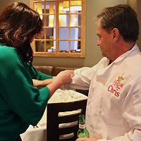 Celebrity Chef Chris Bagley gets the sleeves of his chef's jacket rolled up by Becky Rollins for the Cooking Like the Stars event Sunday evening at Park Heights