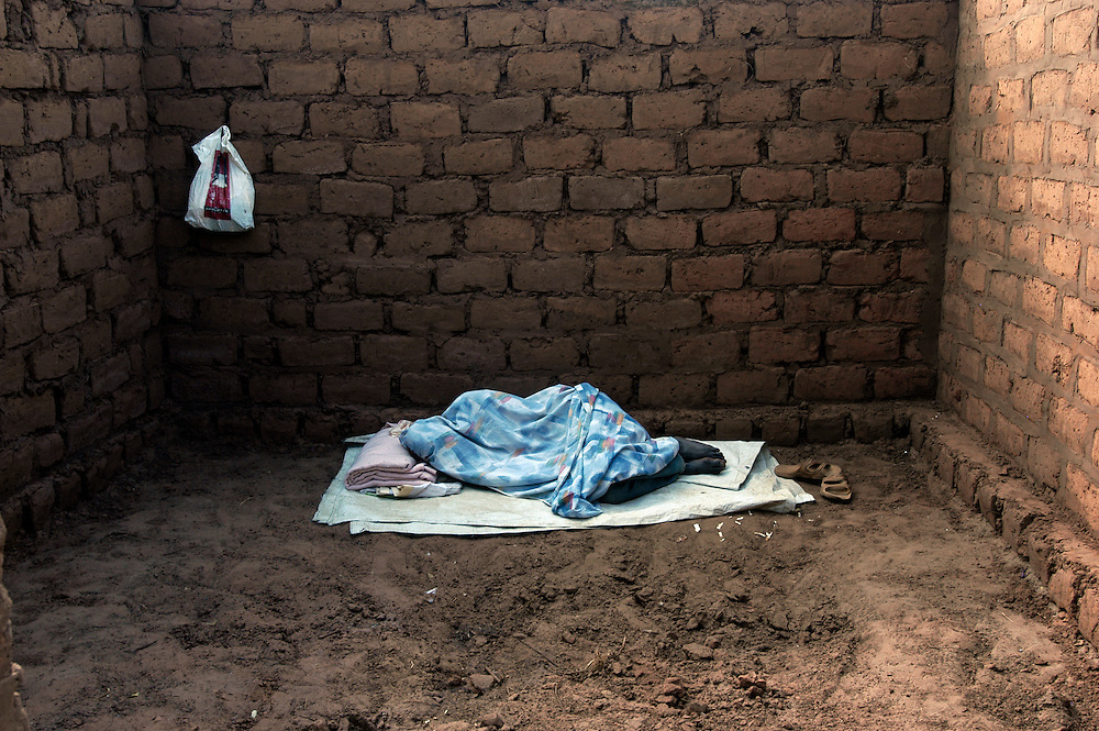 A man sleeps in the four mud brick walls of a half-built house in a village in the eastern province of Moxico..Chifoio, Moxico Province, Angola. 23/07/2009..Photo © J.B. Rusell